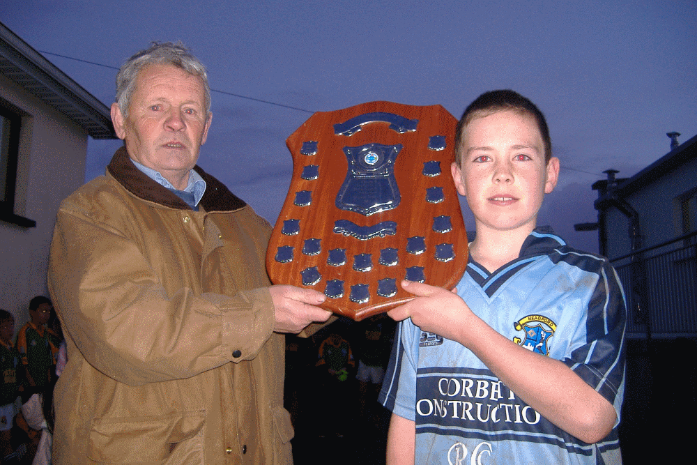 Willie Gannon presents the Stephen Gannon Memorial Shield to Headford Captain Rory Corbett after his side defeated Renvyle after extra time in the 2006 County U-12 Division 3 final at Tullycross.