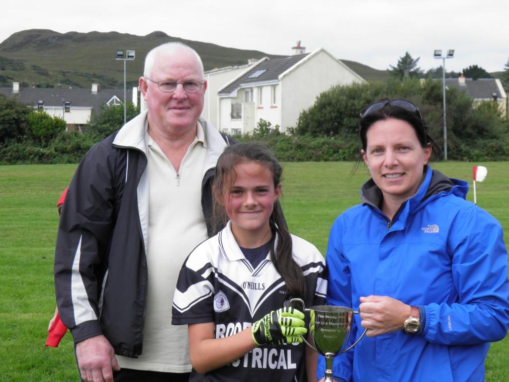 Caption, Presentation of Cup Gráinne Mhaols Captain, Megan Walsh was presented with the West Galway U11A Cup by Peil na mBan Administrators, Philomena Ní Fhlaithearta and Coíl Ó Ceallaigh.   Photo courtesy of Bernie Coyne.